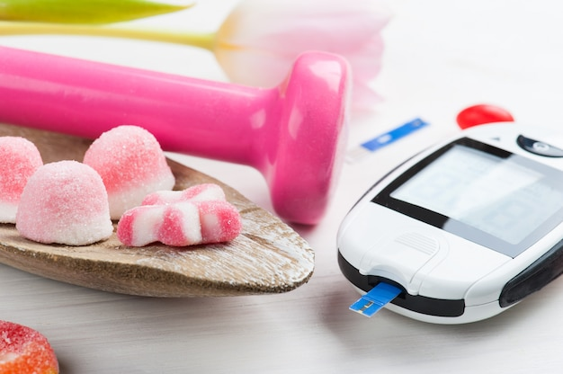 Rosa hantel, süßigkeiten und blutzuckermessgerät Premium Fotos