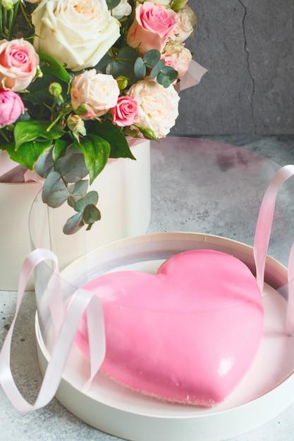 Rosa herzförmiger moussekuchen und ein großer strauß schöner blumen Premium Fotos