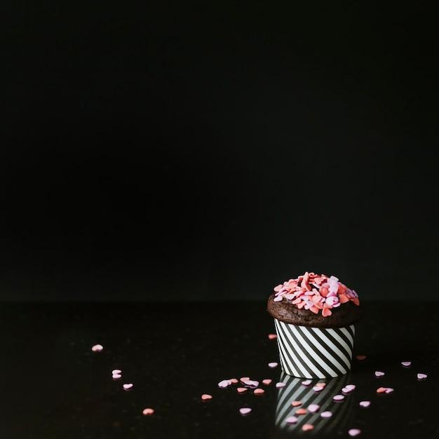 Rosa herzform besprüht auf kleiner kuchen über schwarzem hintergrund Kostenlose Fotos