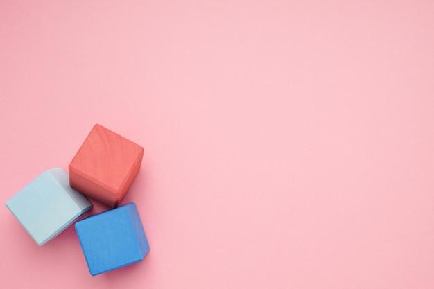 Rosa hintergrund mit bunten hölzernen würfeln. kreativität spielzeug. bausteine für kinder. Premium Fotos