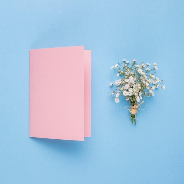 Rosa hochzeitseinladung nahe bei dekorativer blume Kostenlose Fotos