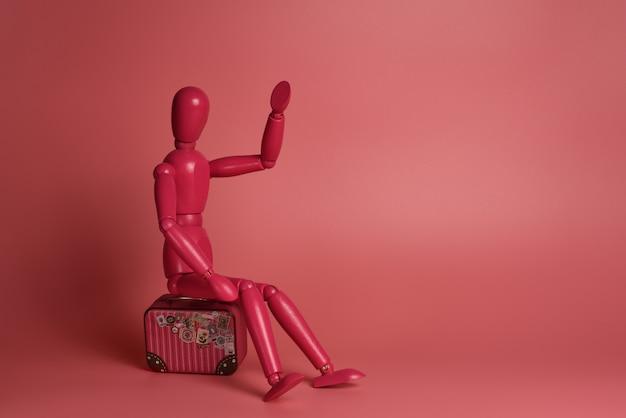 Rosa hölzerner mann sitzt auf einem koffer vor einem rosa hintergrund Premium Fotos