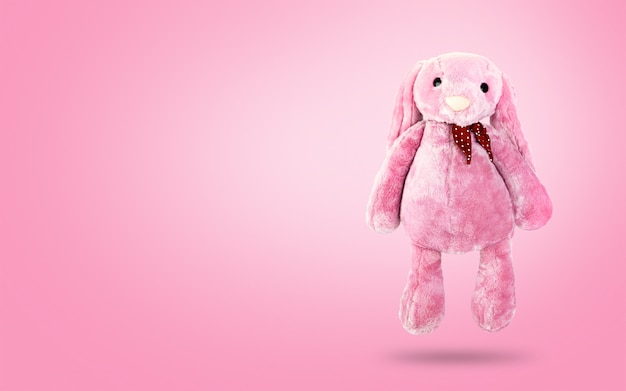 Rosa kaninchenpuppe mit den großen ohren auf süßem hintergrund. süßes kuscheltier und flauschiges fell für kinder. Premium Fotos