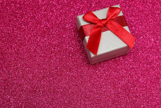 Rosa kasten des geschenks auf funkelndem rosa hintergrund. Premium Fotos
