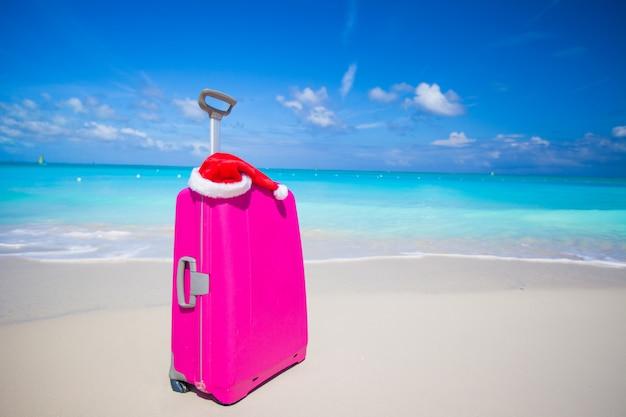 Rosa koffer und santa claus-hut auf weißem sandstrand Premium Fotos