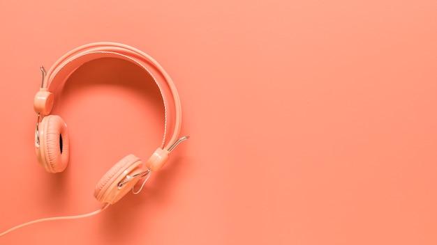 Rosa kopfhörer auf farbiger oberfläche Kostenlose Fotos