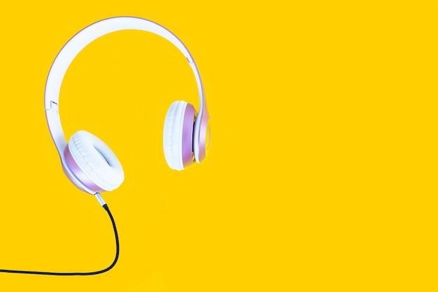 Rosa kopfhörer und schwarzes kabel auf pastellfarbgelbem hintergrund. musik-konzept. Premium Fotos