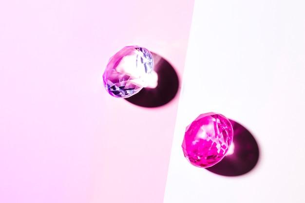 Rosa kristalldiamanten auf rosa und weißem doppelhintergrund Kostenlose Fotos