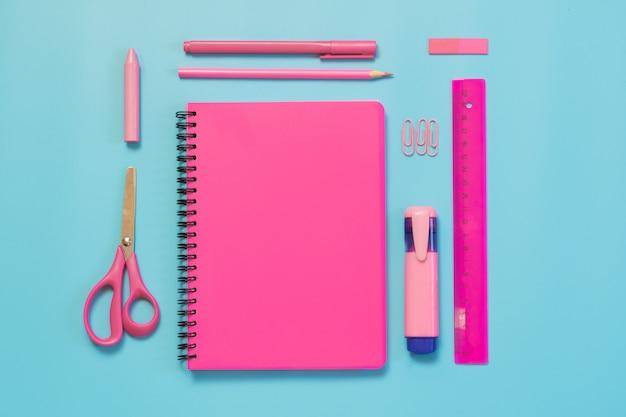 Rosa mädchenhafter schulbedarf, notizbücher und stifte auf schlagkräftigem blau. draufsicht, flach zu legen. kopieren sie platz. Premium Fotos