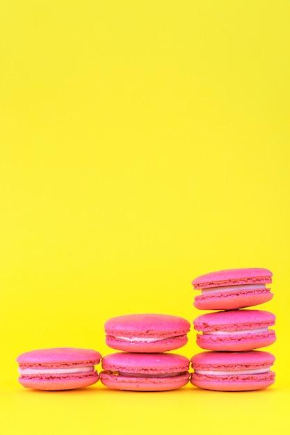 Rosa makronen auf einem gelben hintergrund Premium Fotos