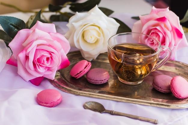Rosa makronen, heißer tee auf silbernem weinlesebehälter verwischten rosenhintergrund Premium Fotos