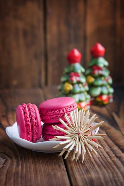 Rosa makronen mit weihnachtsdekorationen auf hölzernem hintergrund Premium Fotos