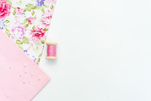 Rosa natürliches gewebe und nähende werkzeuge auf dem weißen holztisch Premium Fotos