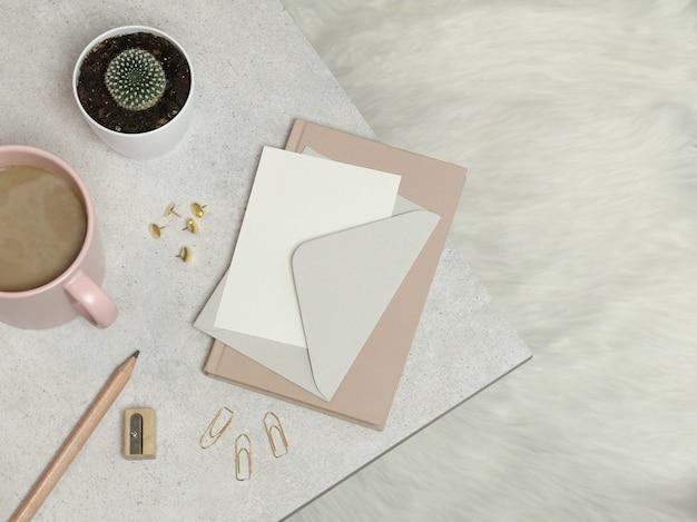Rosa notizbuch, silberner umschlag, bleistift, bleistiftspitzer, büroklammern, tasse kaffee, kaktus auf granittabelle Premium Fotos