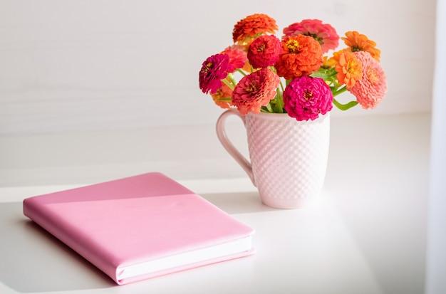 Rosa notizbuch und ein blumenstrauß. Premium Fotos