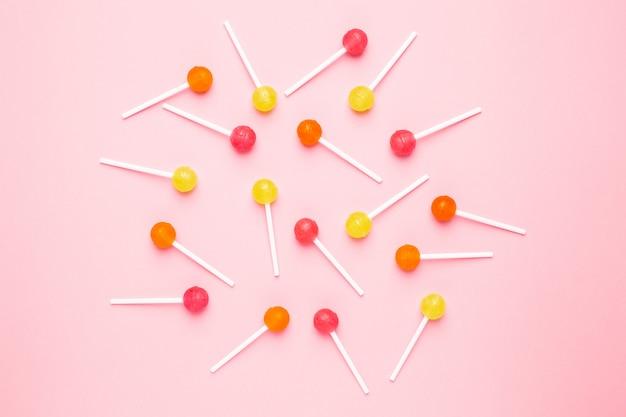 Rosa, orange und gelber süßer süßigkeitslutscher auf pastellrosa Premium Fotos