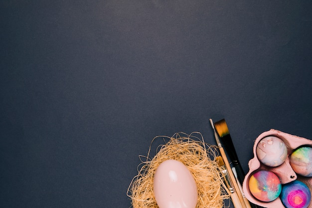 Rosa osterei im nest; pinsel und eierkarton an der ecke des schwarzen hintergrunds Kostenlose Fotos