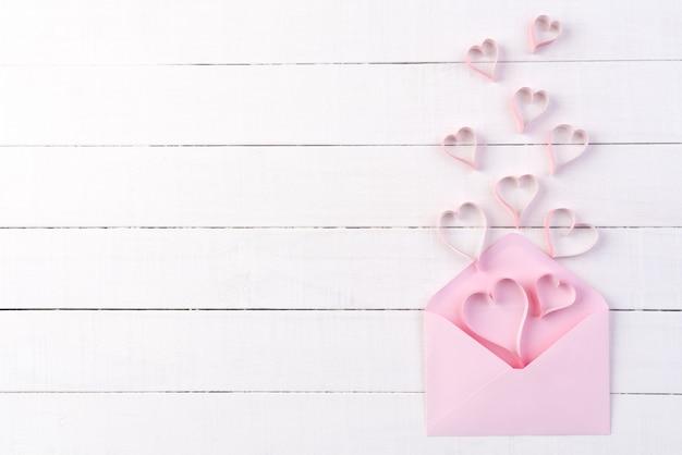 Rosa papierherzen spritzen heraus von der briefabdeckung auf weißem hölzernem hintergrund. Premium Fotos