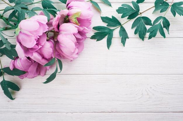 Rosa pfingstrosen und blätter auf hölzernem hintergrund Premium Fotos