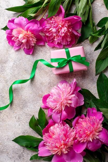 Rosa pfingstrosenblumen und geschenkbox Premium Fotos