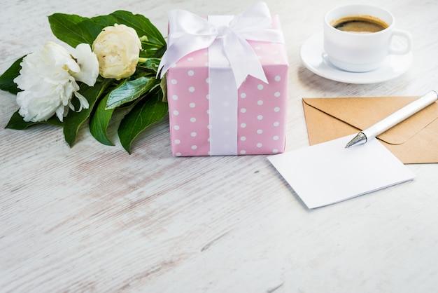Rosa punktierte geschenkbox, leere grußkarte, kraftpapier-umschlag, pfingstrosenblumenstrauß und kaffeetasse über weißer hölzerner rustikaler tabelle. Premium Fotos