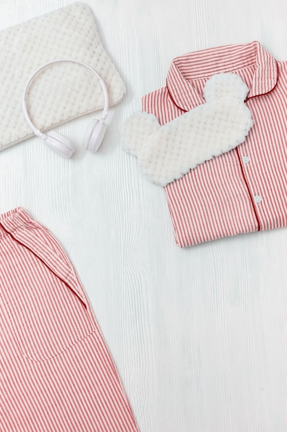 Rosa pyjama, augenmaske zum schlafen, kopfhörer und weiches kissen Premium Fotos