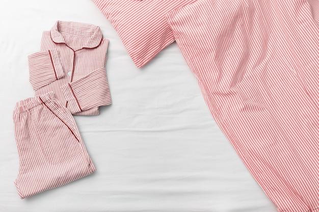 Rosa pyjama klappbett, decke und kissen im schlafzimmer des hauses. Premium Fotos