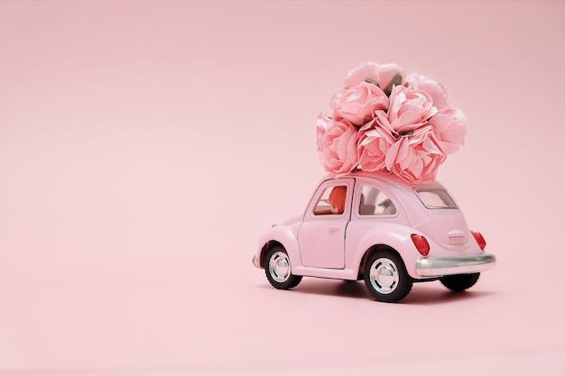 Rosa retro- spielzeugauto, das blumenstrauß von blumen liefert Premium Fotos