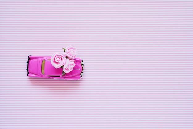 Rosa retro- spielzeugauto, das rosa blumenblumenstrauß auf rosa hintergrund liefert. Premium Fotos