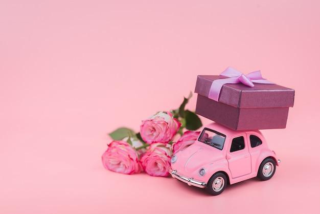 Rosa retro-spielzeugauto liefert eine geschenkbox auf rosa hintergrund. 14. februar postkarte, valentinstag. blumenlieferung. frauentag Premium Fotos