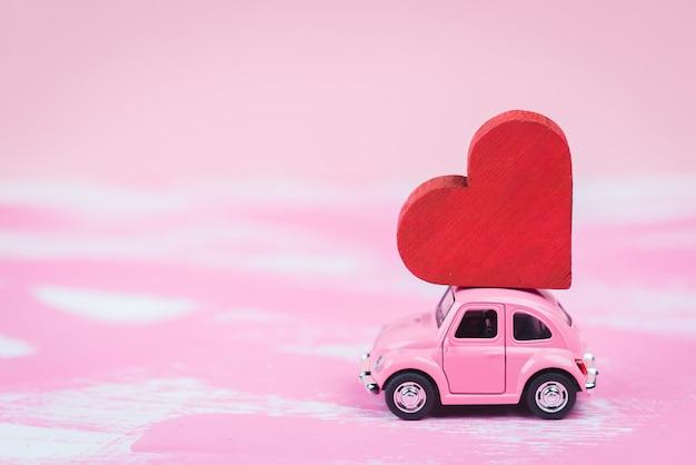 Rosa retro-spielzeugauto liefert einen roten hirsch auf rosa hintergrund. 14. februar postkarte, valentinstag. blumenlieferung. frauentag Premium Fotos
