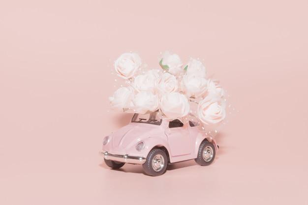 Rosa retro- spielzeugauto mit blumenstrauß von weiß Premium Fotos