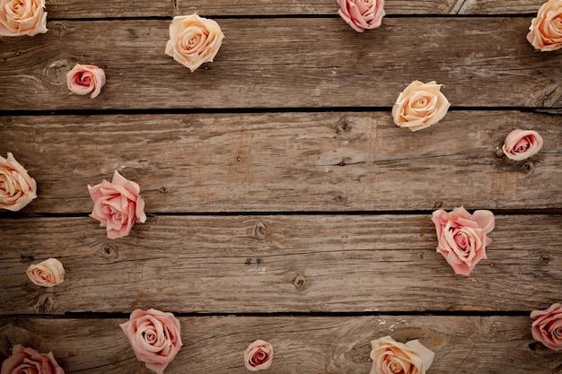 Rosa rosen auf braunem hölzernem hintergrund Kostenlose Fotos
