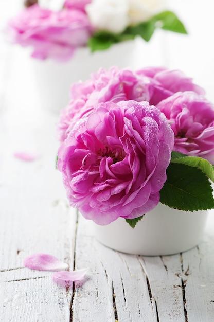 Rosa rosen auf dem holztisch Premium Fotos