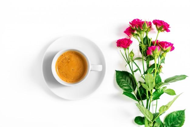 Rosa rosen mit einem tasse kaffee lokalisiert auf einem weißen hintergrund Premium Fotos