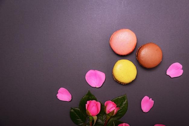 Rosa rosen und drei bunte makronen Premium Fotos