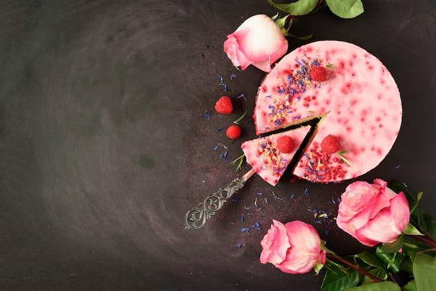 Rosa rosen und köstlicher himbeerkuchen mit frischen beeren, rosmarin, trockenen blumen. vegetarisches, veganes lebensmittelkonzept Premium Fotos