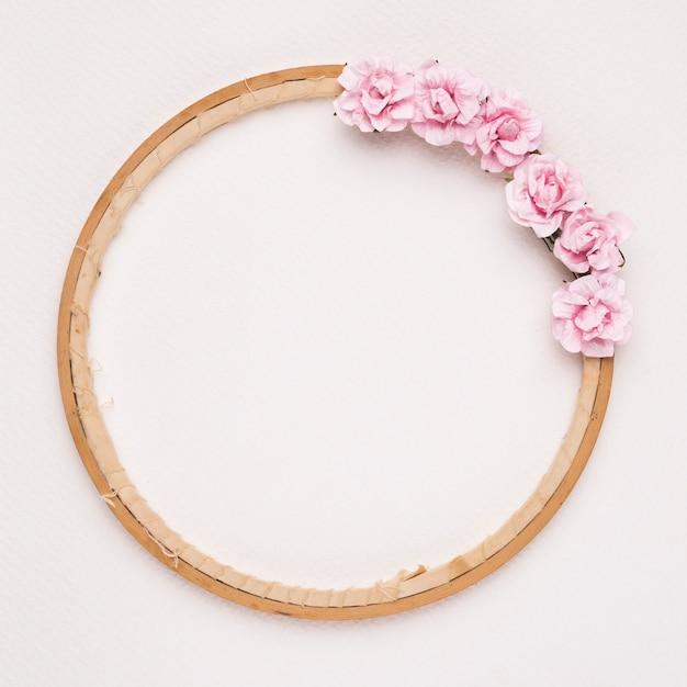Rosa rosen verziert auf kreisholzrahmen gegen weißen hintergrund Kostenlose Fotos