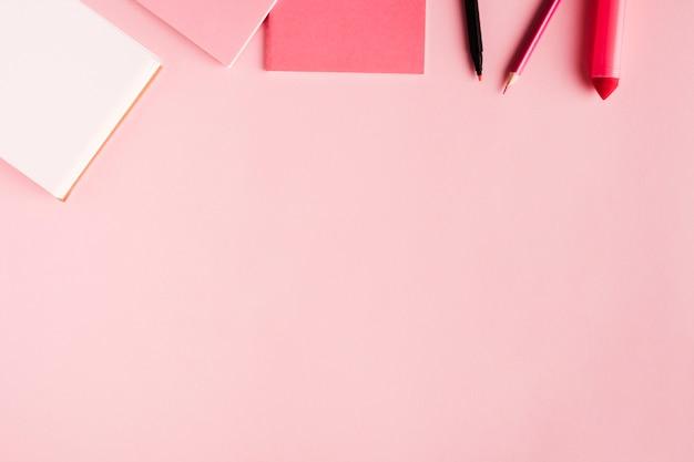 Rosa schulwerkzeuge auf farbiger oberfläche Kostenlose Fotos