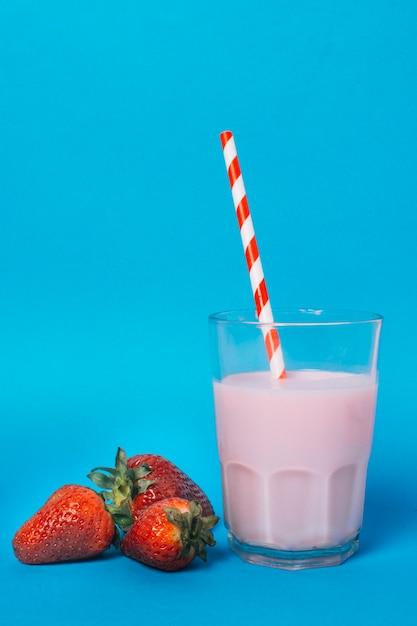 Rosa smoothie nahe bei erdbeeren mit blauem hintergrund Kostenlose Fotos