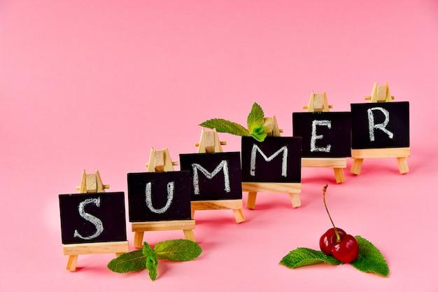 Rosa sommerhintergrund. schwarze karten mit buchstaben sommer, minze und eine kirsche. Premium Fotos