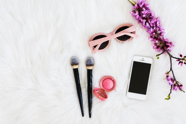 Rosa sonnenbrillen; lila blumenzweig; kompaktes gesichtspuder; make-up-pinsel und handy auf pelzhintergrund Kostenlose Fotos