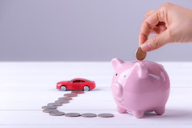 Rosa sparschwein, münzen und ein auto. frauenhand, die münze zum sparschwein setzt. Premium Fotos