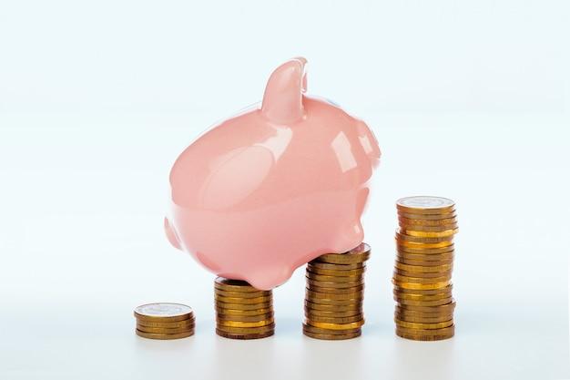 Rosa sparschwein und münzen lokalisiert auf weiß Premium Fotos