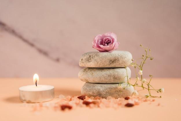 Rosa stieg über den stapel der badekurortsteine mit beleuchteter kerze; himalayasalze und babyatmungsblumen auf farbigem hintergrund Kostenlose Fotos