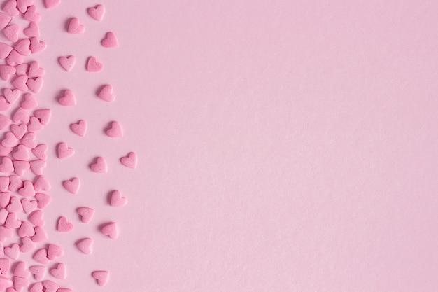 Rosa süßwarenherzen gelegen auf der linken seite auf rosa hintergrund, grußkarte Premium Fotos