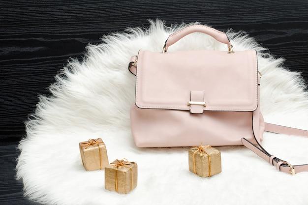 Rosa tasche und geschenkbox auf weißem pelz Premium Fotos