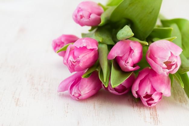Rosa tulpen auf weißem hölzernem Premium Fotos