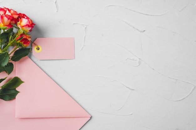 Rosa umschlag mit blumen, draufsicht. romantischer brief Premium Fotos