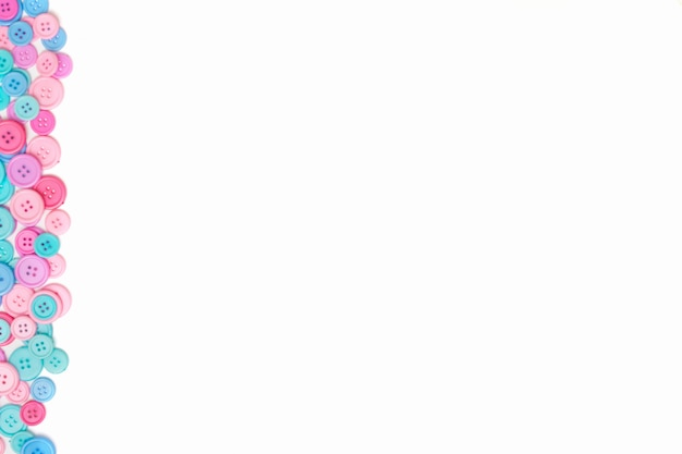 Rosa und blaue nähende knöpfe auf weißem hintergrund. Premium Fotos